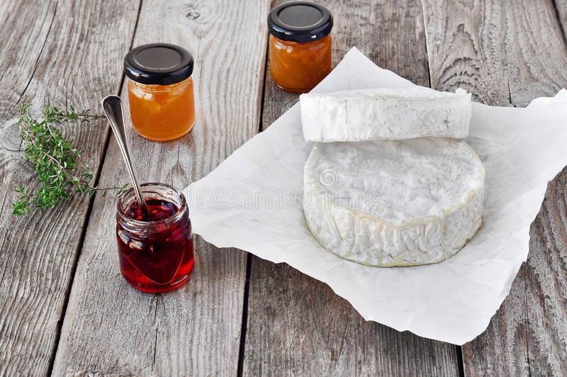 French soft cheese with a different jam on the natural wood back. Graund royalty free stock photography