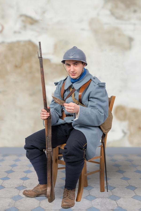French soldier 1914 1918, sitting on chair, reading letter. A French soldier 1914 1918, sitting on chair, reading letter royalty free stock image