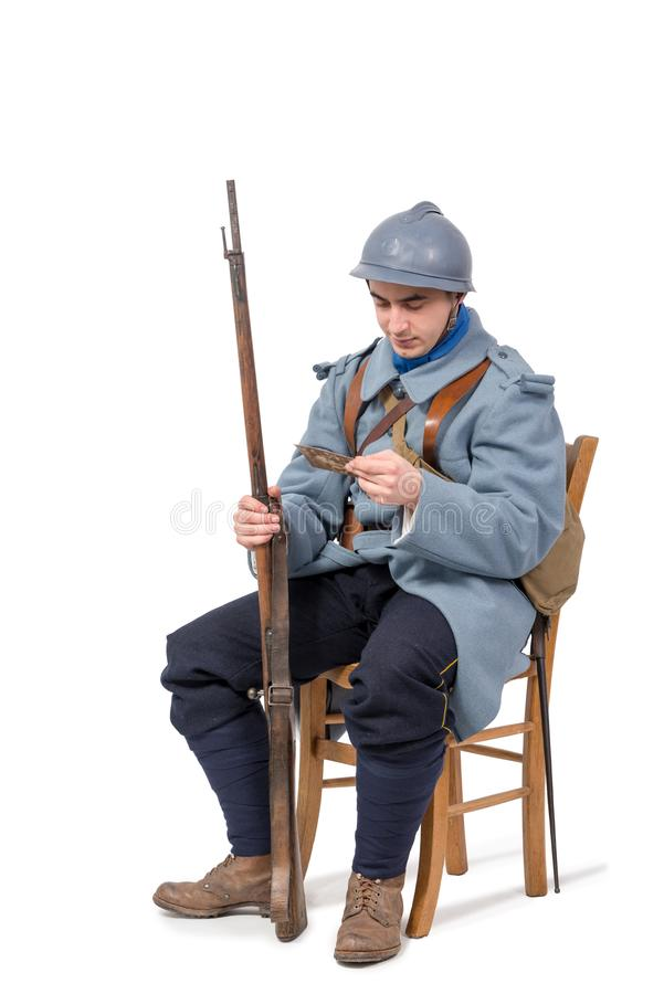 French soldier 1914 1918, sitting on chair, reading letter isolated on white background. French soldier wwi, 1914 1918, sitting on chair, reading letter isolated stock images