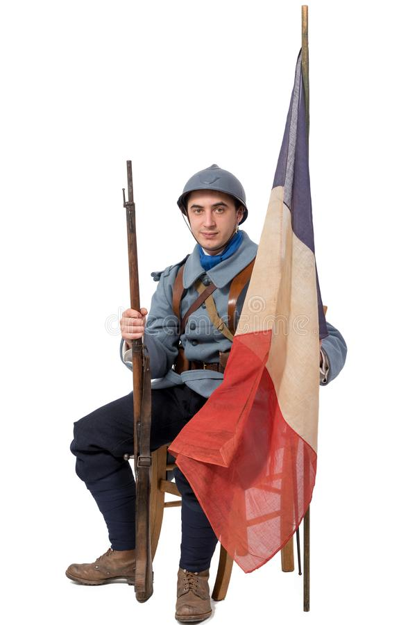 French soldier, 1914 1918 sitting with flag, isolated on white. A French soldier, 1914 1918 sitting with flag, isolated on white background royalty free stock photo