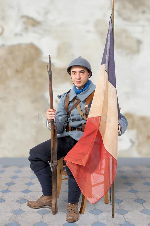 French soldier, 1914 1918 sitting with tricolour flag. A French soldier, 1914 1918 sitting with tricolour flag royalty free stock image