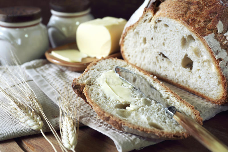 French sourdough bread and butter. On dark wooden chopping board stock photos