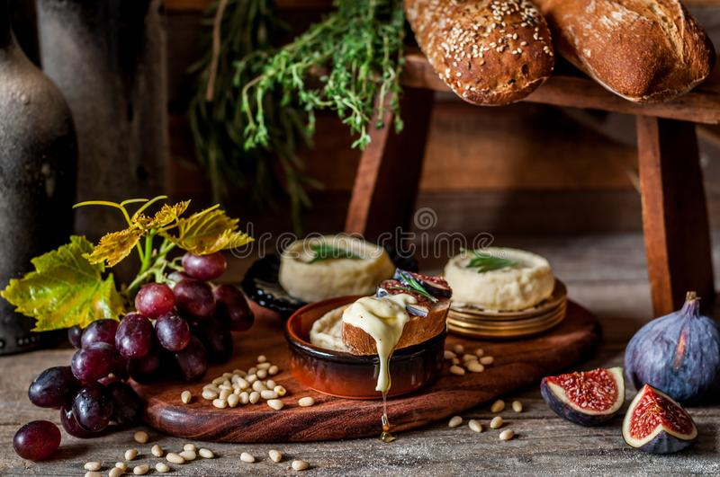 French Stinky Cheese. Soft Spreadable French Stinky Cheese on a Slice of Bread with Fruit and Pine Nuts royalty free stock photo