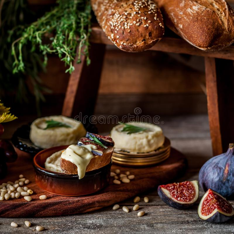 French Stinky Cheese. Soft Spreadable French Stinky Cheese on a Slice of Bread with Fruit and Pine Nuts, square royalty free stock image