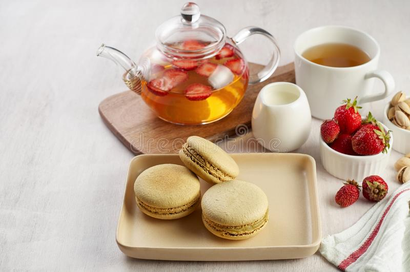 French strawberry pistachio macaron with berries tea. Afternoon tea still life royalty free stock images