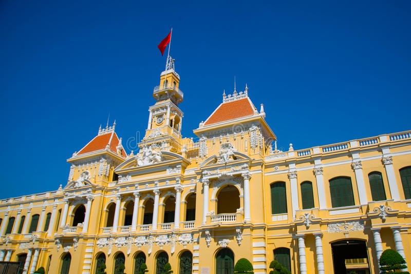 French style of building in Vietnam, Asia. Beautiful Ho Chi Minh City Hall. Facade of house with ornate design. Red flag contrasts stock photos