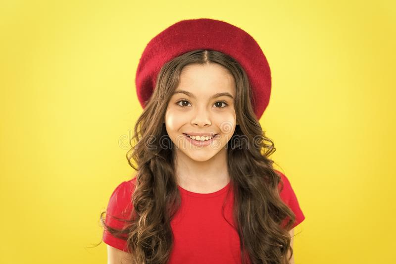 French style inspiration. Adorable small girl wearing red beret in fashion style. Little cute child with beautiful long. Hair style on orange background. Her stock photo