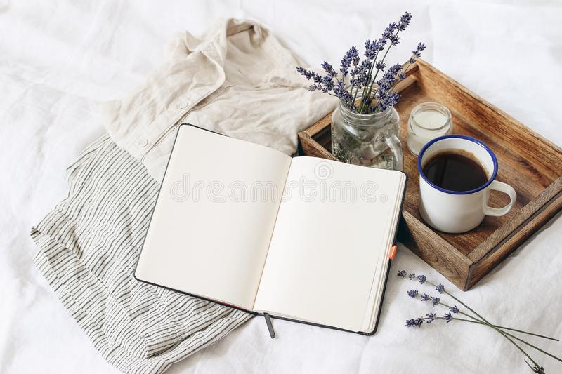 French summer still life. Feminine lifestyle composition. Cup of coffee, lavender flowers bouquet, candle on wooden tray. Linen shirt nad trousers on bed royalty free stock photos