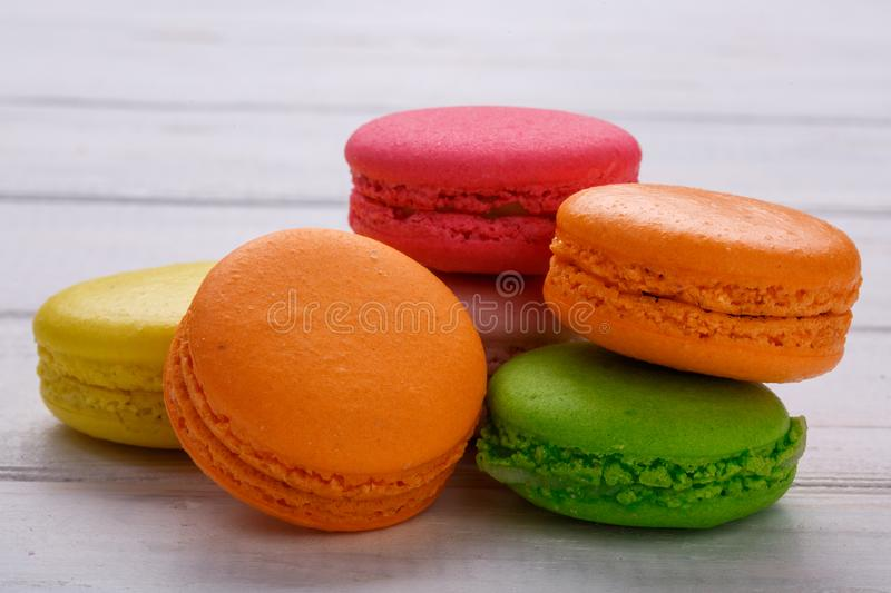 A french sweet delicacy, macaroons variety closeup. White wooden background royalty free stock image