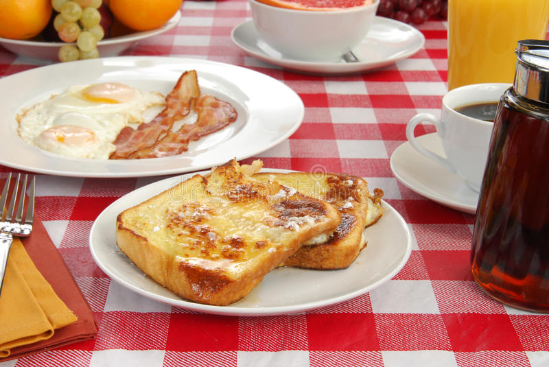 French toast with bacon and eggs. A plate of french toast with bacon and fried eggs stock photo