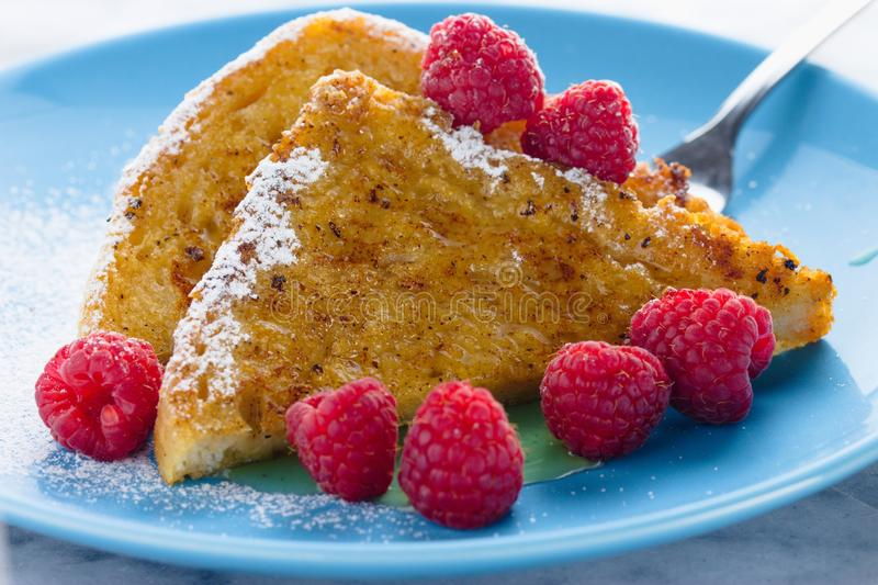 French toast with honey,sugar and raspberries royalty free stock photos