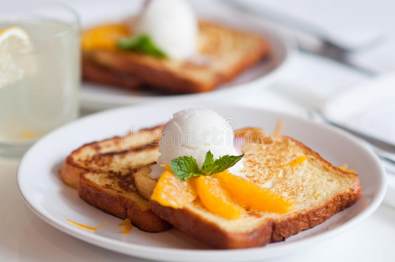 French toasts with ice cream and orange slices stock photography