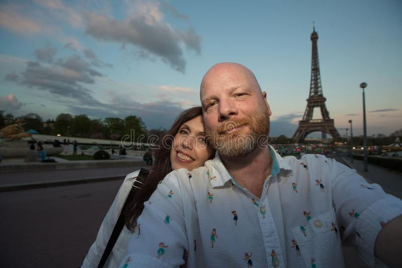 French tourists at the Eiffel Tower in Paris. Happy Couple Takes a selfie near the Eiffel Tower in Paris, France royalty free stock photo