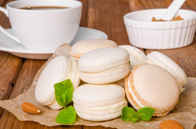 French traditional dessert macarons with vanilla and white chocolate cream. On wooden background stock photography