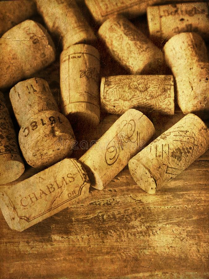 French wine corks close up on wood sepia vintage. Used French wine corks on old wood background sepia and vintage photo effect royalty free stock images
