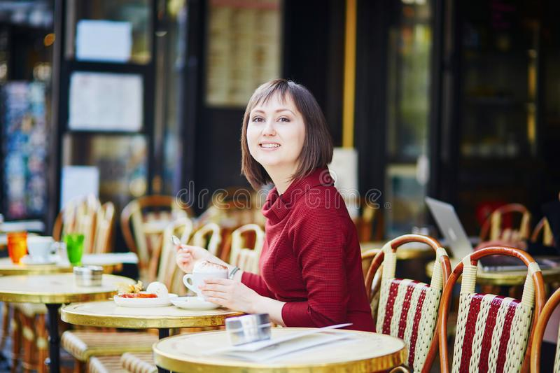French woman drinking coffee in outdoor cafe in Paris, France royalty free stock image