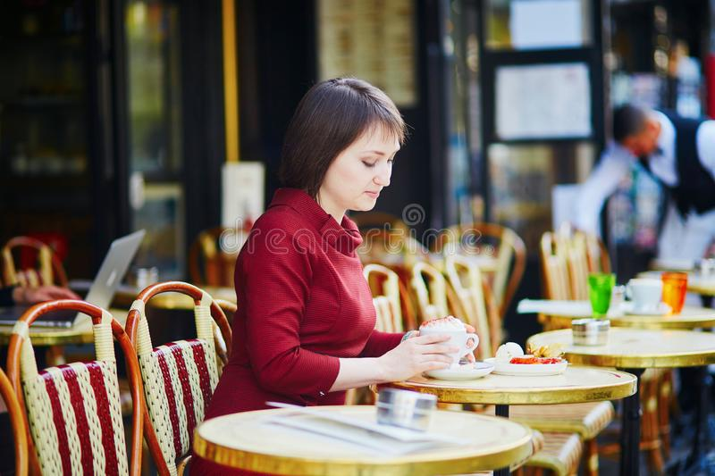French woman drinking coffee in outdoor cafe in Paris, France royalty free stock images