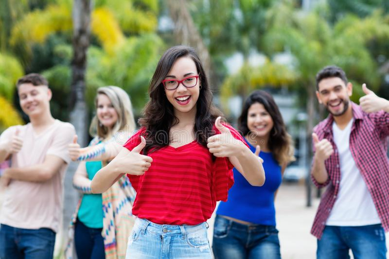 French woman with glasses showing thumb up with group of young adults royalty free stock photography