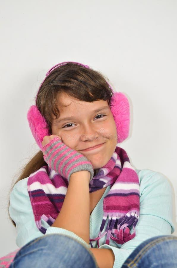 Frendly flicka med öramuffs och klippte handskar arkivbilder