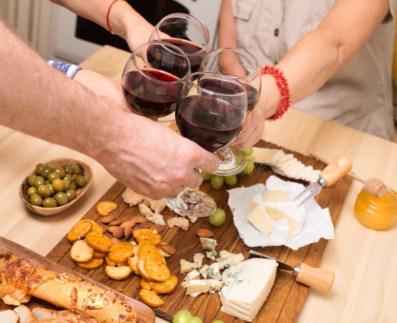 Frends που τρώει το τυρί με τα σταφύλια και που πίνει το κρασί στο σπίτι μαζί, έννοια κομμάτων τυριών στοκ φωτογραφία