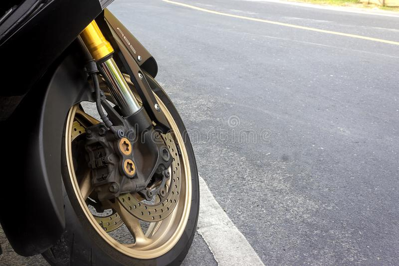 Freno de disco del calibrador y del ABS de la rueda delantera de la estancia de la motocicleta en el camino fotografía de archivo
