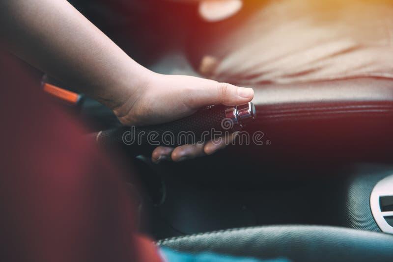 Freno di mano dell'automobile della tenuta della mano dell'autista delle donne del primo piano immagini stock