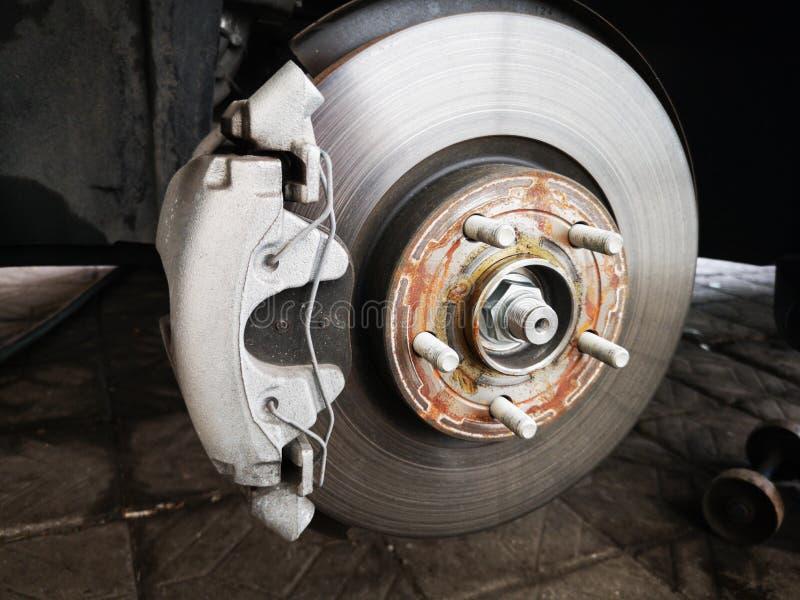 Freno a disco sull'automobile in corso di nuova sostituzione della gomma L'orlo è rimosso che mostra il rotore ed il calibro Fine fotografia stock