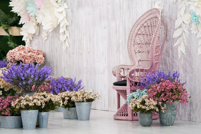 Frente de bambú de la silla del vintage de lujo del contexto de madera blanco y mucho flor alrededor foto de archivo libre de regalías