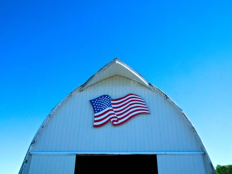Frente del granero blanco con la bandera americana en la granja de Minnesota fotos de archivo libres de regalías