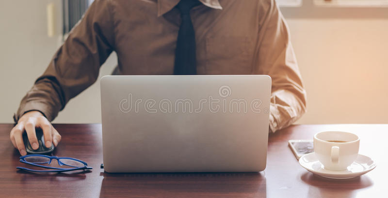 Frente del hombre de negocios usando el ordenador portátil que trabaja en oficina con el teléfono celular y el café imagenes de archivo