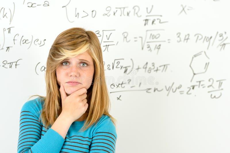 Frente desesperado de la muchacha del estudiante del tablero de la matemáticas fotos de archivo