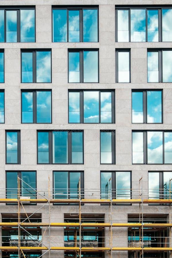 Frente moderno de la fachada del edificio de oficinas en parte, con el andamio imagen de archivo libre de regalías