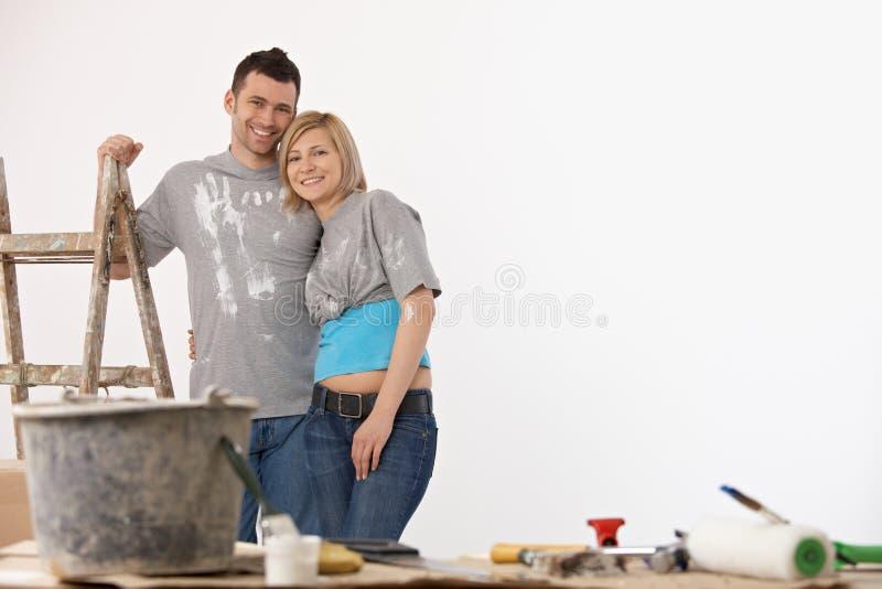 Frente permanente de los pares felices de la pared blanca pintada fotos de archivo libres de regalías