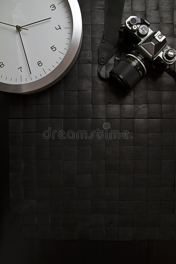 The frenzy of today`s times in contrast with the past. A modern design wall clock next to a vintage camera on a black background royalty free stock photos