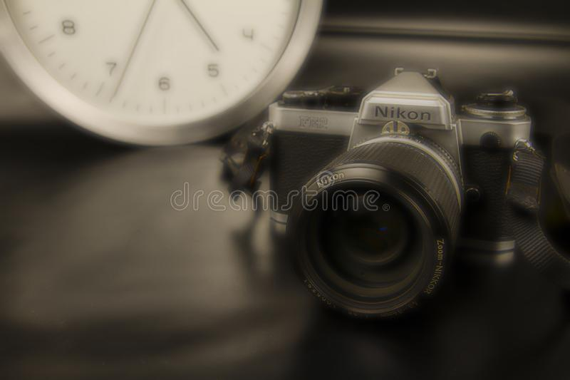 The frenzy of today`s times in contrast with the past. A modern design wall clock next to a vintage camera on a black background stock images