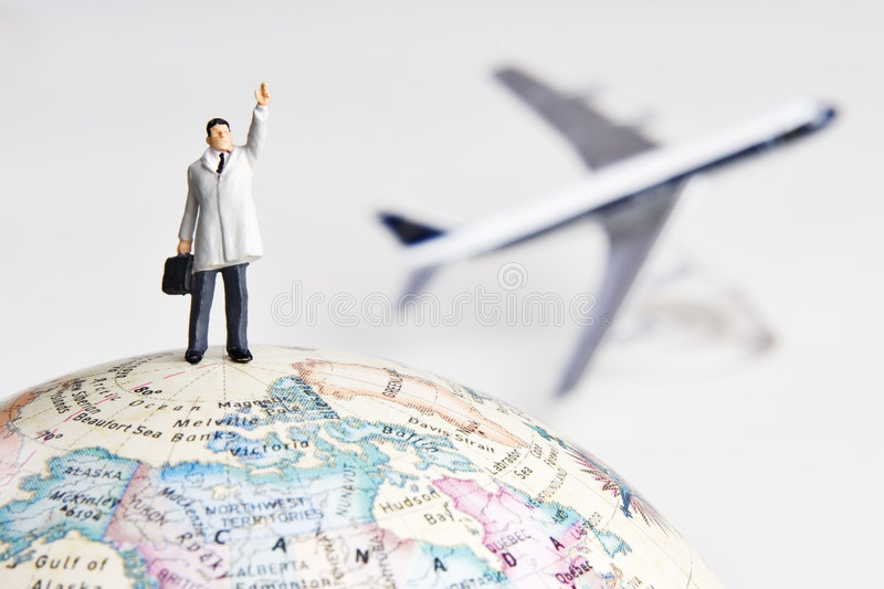 Frequent flier. Business figurine on earth globe with toy airplane in background royalty free stock image