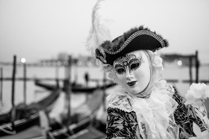 Frequentatore maschio di carnevale in costume tradizionale e maschera che sta con di nuovo a Grand Canal, gondole nei precedenti fotografia stock libera da diritti