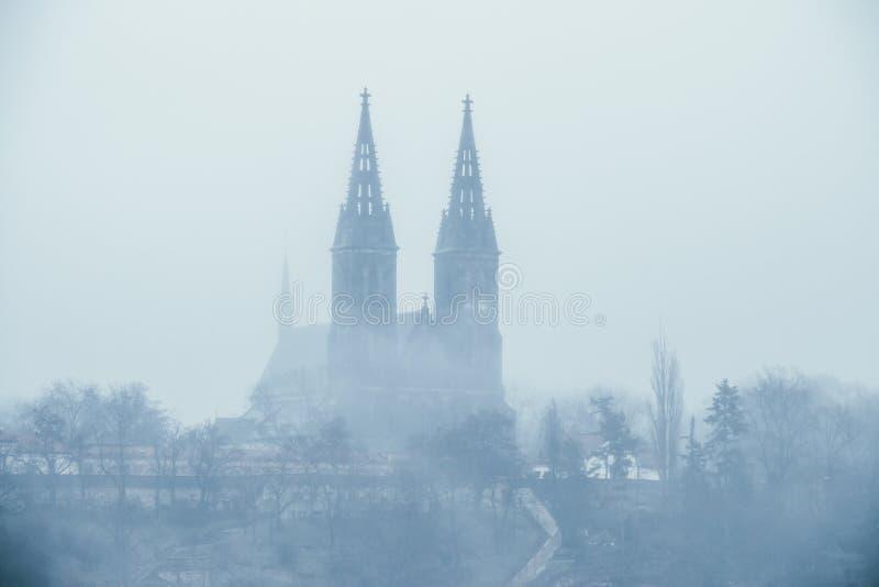 Frequentierte Kirche - alte Vysehrad-Basilika von St Peter und von Pavel bedeckt im Nebel während des nebeligen Tages stockfotografie