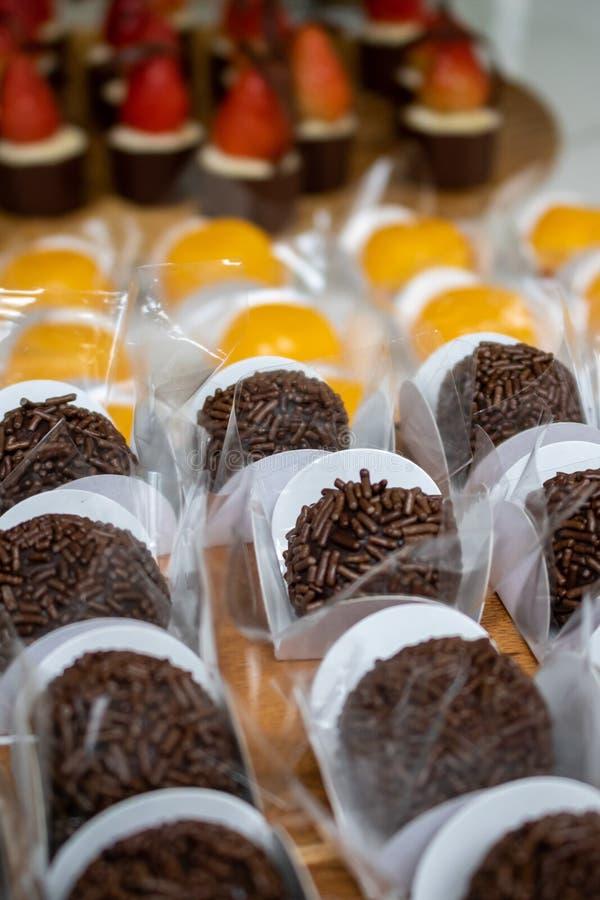 Fresa apetitosa, caramelo de la crema y de chocolate, un postre brasileño hecho con los huevos y coco Quindim, Brigadeiro - Braz  fotos de archivo