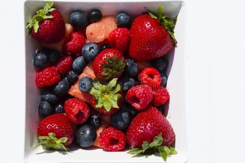 Fresa, arándano, frambuesa, sandía en el cuenco cuadrado, fondo blanco imagenes de archivo