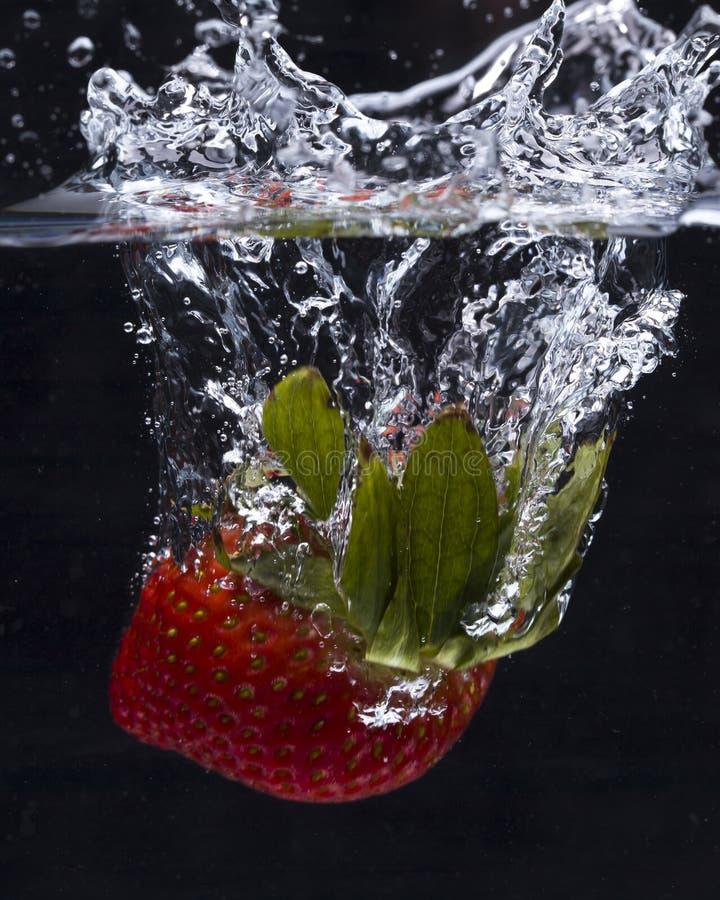 Fresa caída en el agua que hace un chapoteo fotografía de archivo