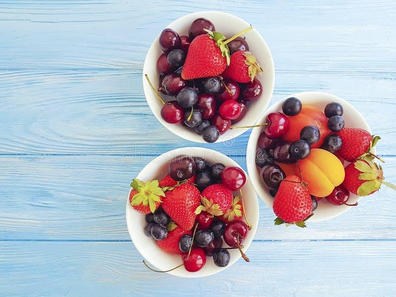 Fresa, cereza, arándano, albaricoque delicioso de la cosecha de la vitamina de la placa en un fondo de madera imagen de archivo