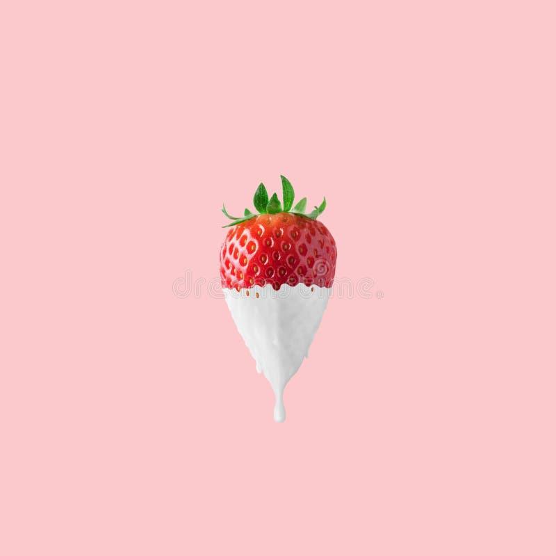 Fresa con la pintura blanca del goteo en fondo rosado Concepto mínimo de la comida foto de archivo libre de regalías