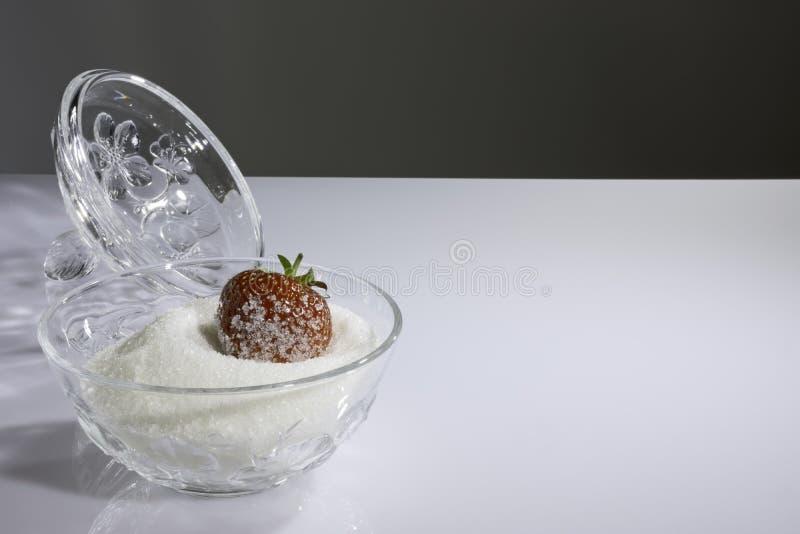 Fresa cubierta con el azúcar en cuenco con el azúcar imagenes de archivo