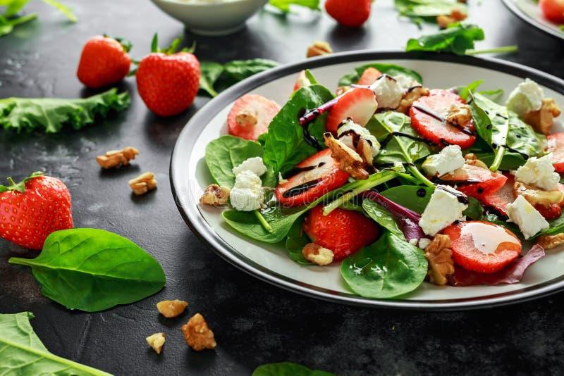 Fresa de la fruta del verano, ensalada de la espinaca con la nuez, vinagre balsámico del queso feta, col rizada En una placa comi imagen de archivo