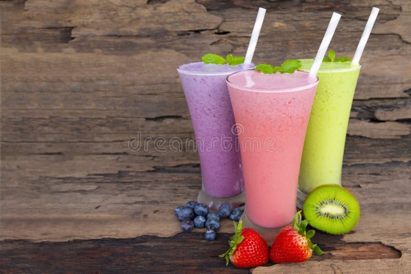 Fresa del arándano y batido de leche colorido del zumo de fruta de los smoothies del kiwi fotografía de archivo libre de regalías