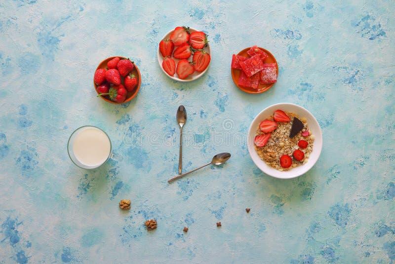 Fresa, muesli, leche y placer turco en una tabla de la turquesa Hora por tiempo de la demostración de las cucharas del desayuno imagen de archivo libre de regalías