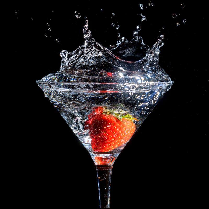 Fresa que salpica en el vidrio de martini imagen de archivo