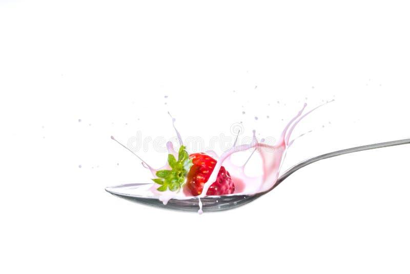 Fresa que salpica en una cuchara por completo del yogur fotografía de archivo