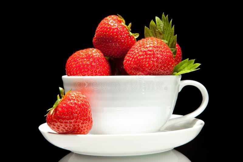 Fresa roja en la taza blanca en un fondo negro foto de archivo